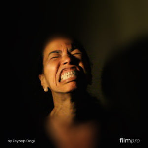 The close up photo of a woman's face, brightly lit against a dark backdrop. Her eyes are screwed shut and she is showing and grinding her teeth as if in pain or rage.