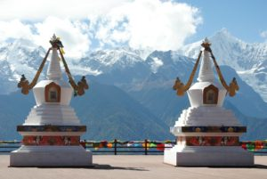The photo of what appears to be two shrines or temple-like sculptures, bright white with gold and coloured decorations, set against a mountain landscape and sky covered in light cloud. A fence is also visible behind the shrines, covered in coloured bunting.